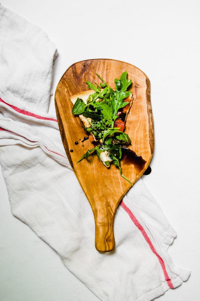 Tomato and Arugula Pizza on wooden board with white napkin