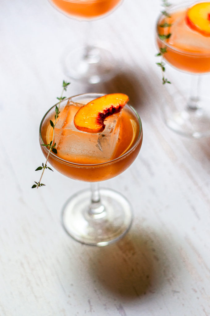 Cocktail with peach and thyme garnish