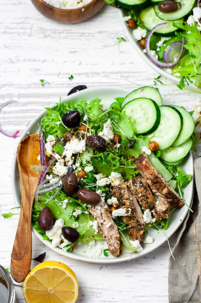 greek chicken salad with crispy chickpeas in a bowl with a spoon