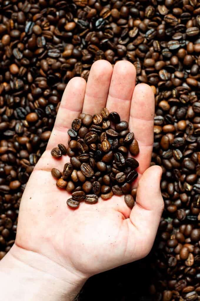 Man's hand holding coffee beans