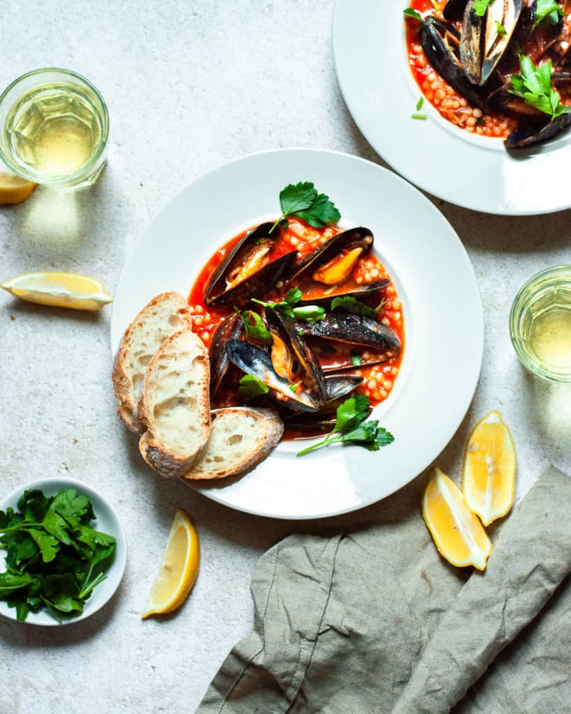 Mussels with Israeli Couscous and Tomato in a bowl with bread, lemons, and wine