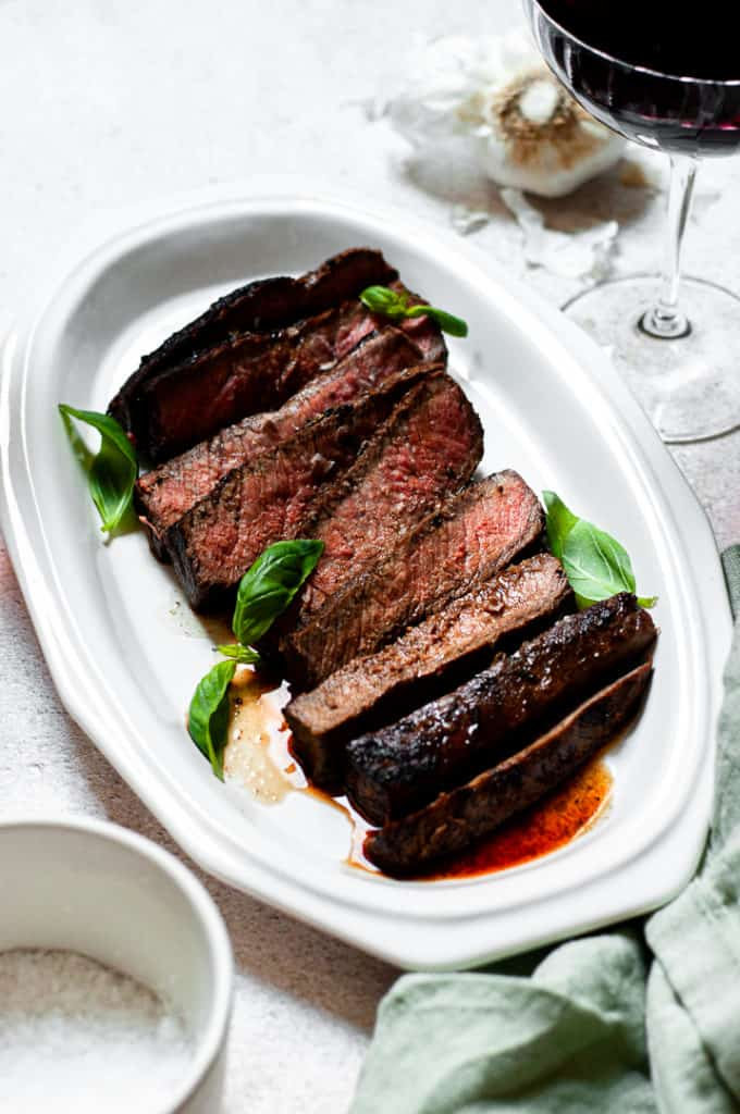 Skirt steak on a platter with wine and garlic
