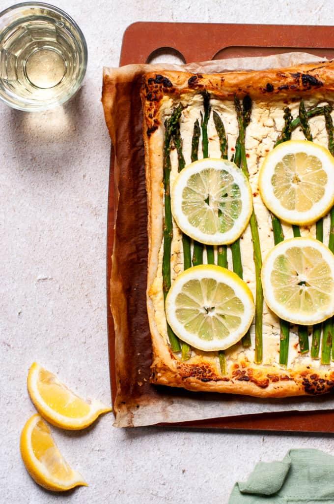 Asparagus tart with lemon slices on a cutting board