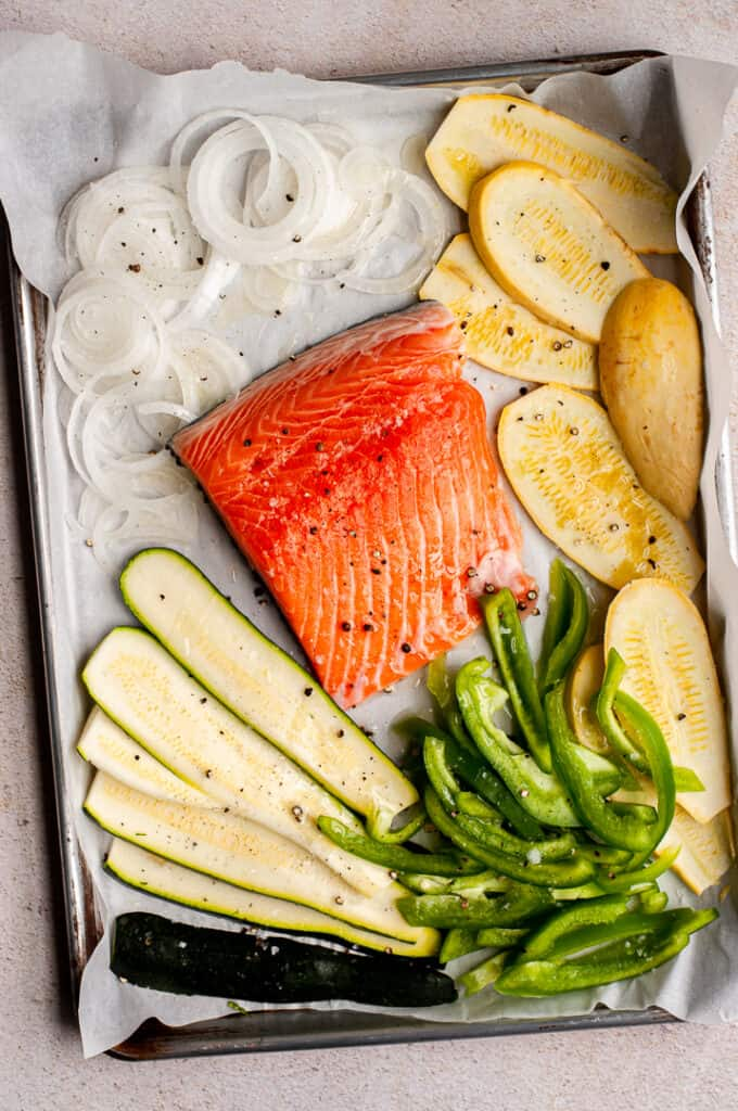 Raw salmon and vegetables on a baking tray