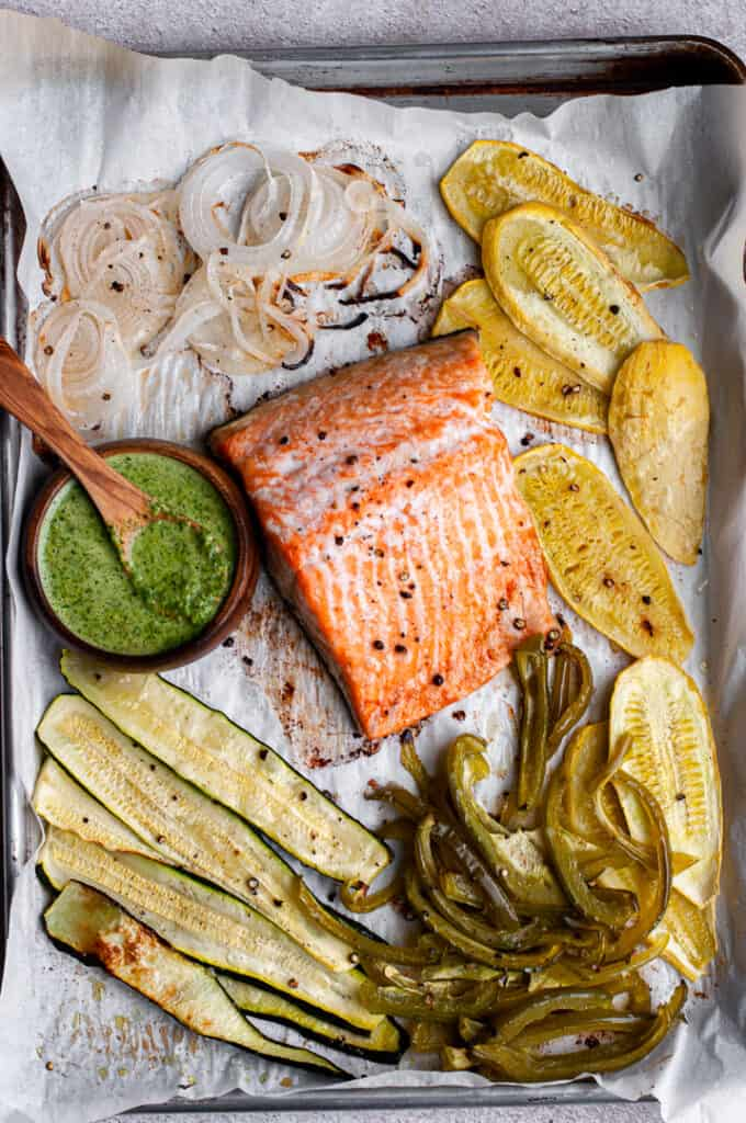 Salmon, vegetables, and cilantro sauce on a baking tray