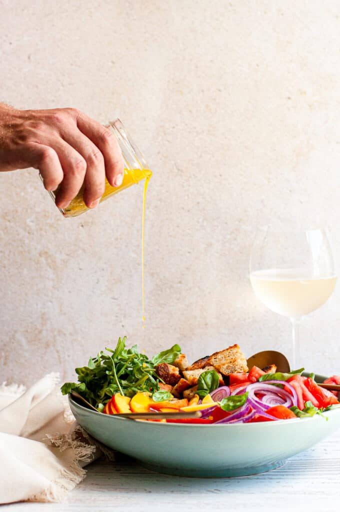 Man pouring dressing on salad