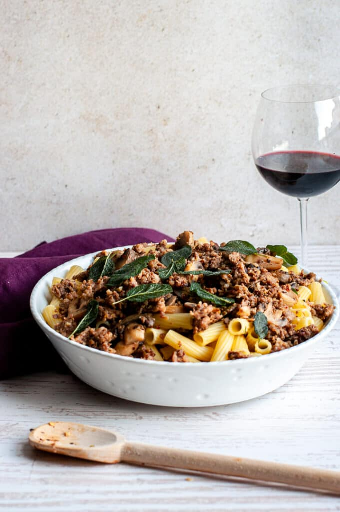 Sausage and Mushroom Rigatoni with Crispy Sage in a bowl with a wine glass