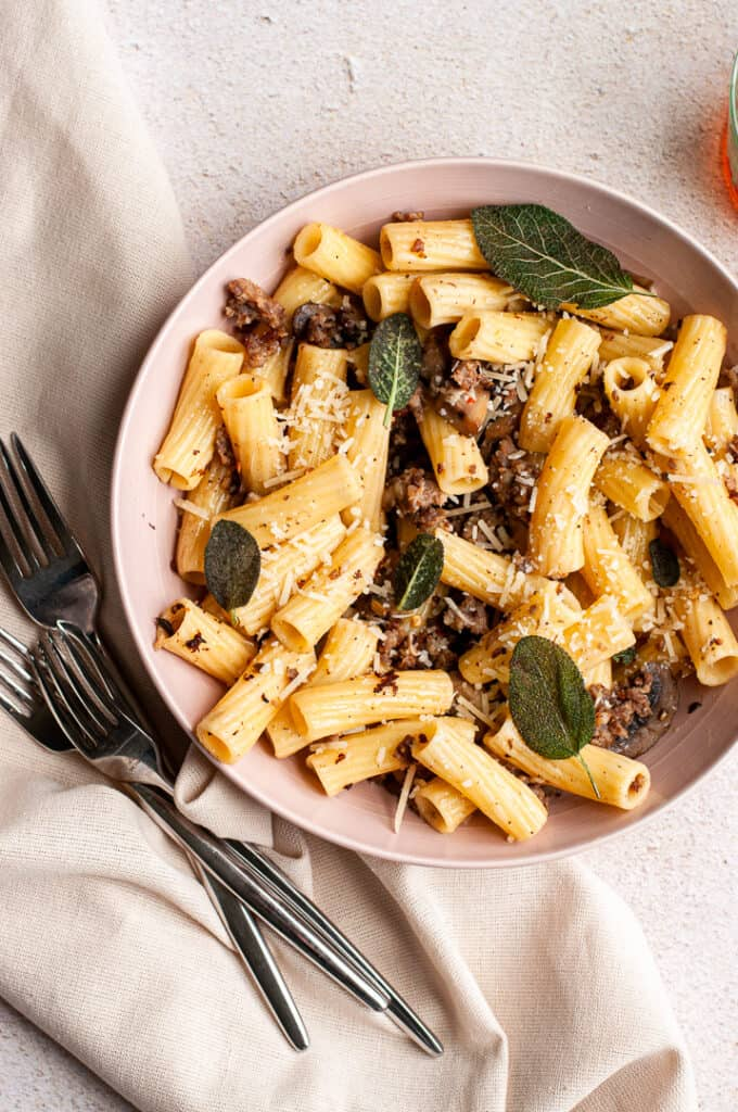 Sausage and Mushroom Rigatoni with Crispy Sage in a bowl with forks
