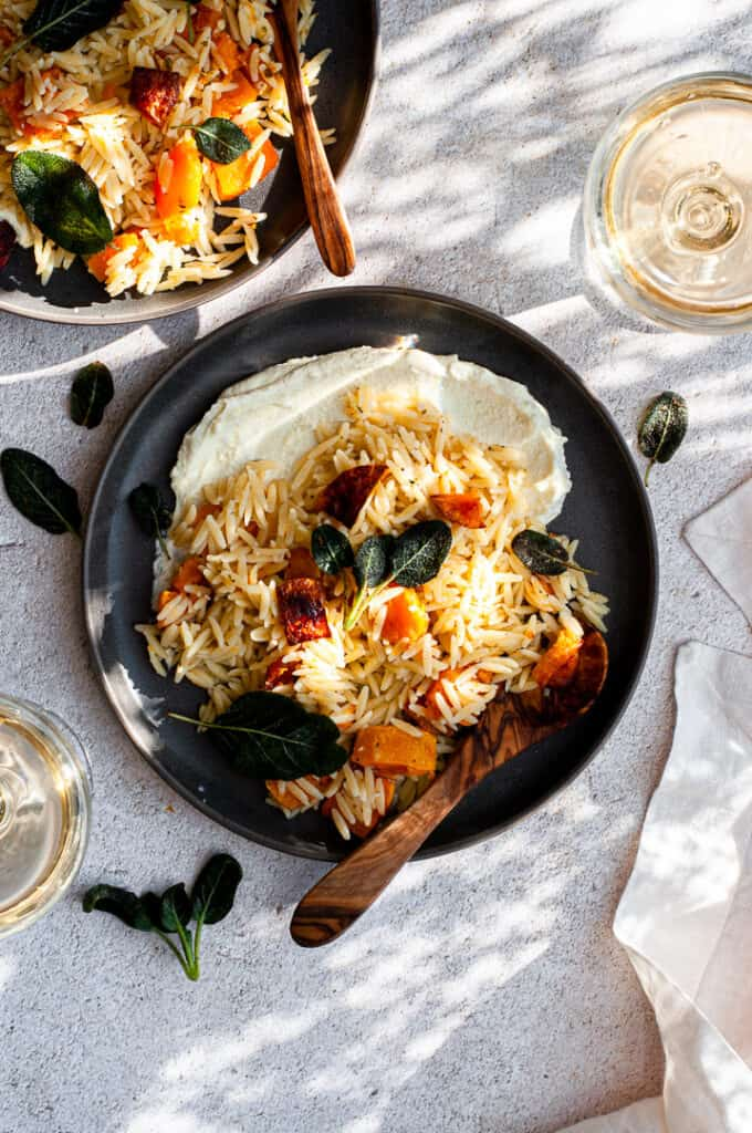Butternut Squash Orzo with Whipped Feta in a large bowl with a glass of wine